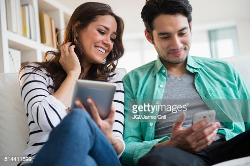 Couple using technology together on sofa
