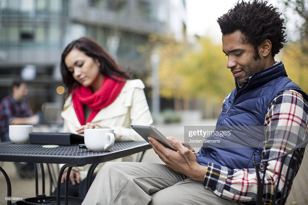 A couple using theier digital tablets. : Stock Photo