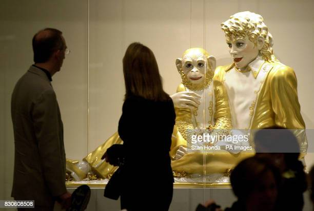 A couple views the 'Michael Jackson and Bubbles' sculpture by American artist Jeff Koons just before the Contemporary Art sale at Sotheby's auction...