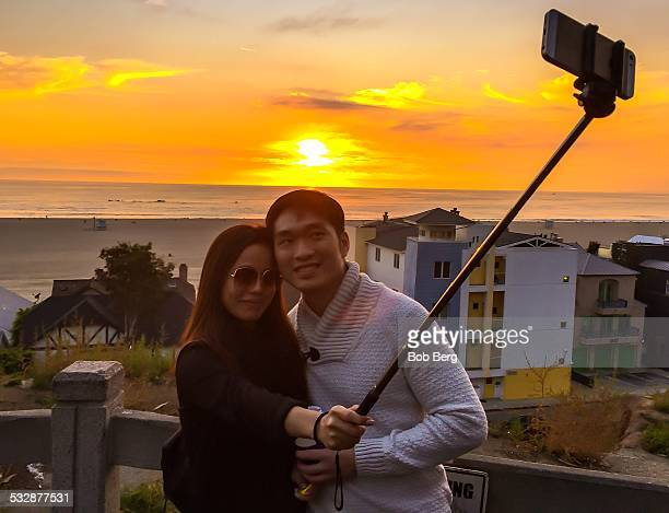 Santa Monica Ca January 9 2015 A couple visiting from Hong Kong take a couple selfie with a selfie stick of themselves against the sunset on the...