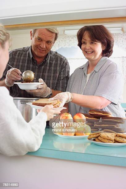 Couple volunteering in soup kitchen