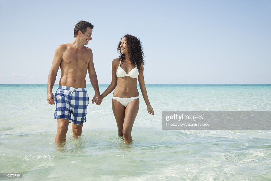 Couple wading hand in hand at the beach