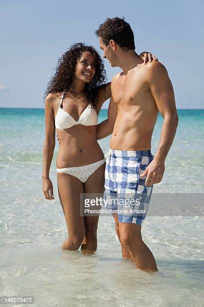 Couple wading in water at the beach