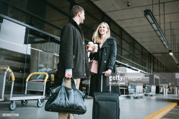 Couple Wait for Ride at Airport