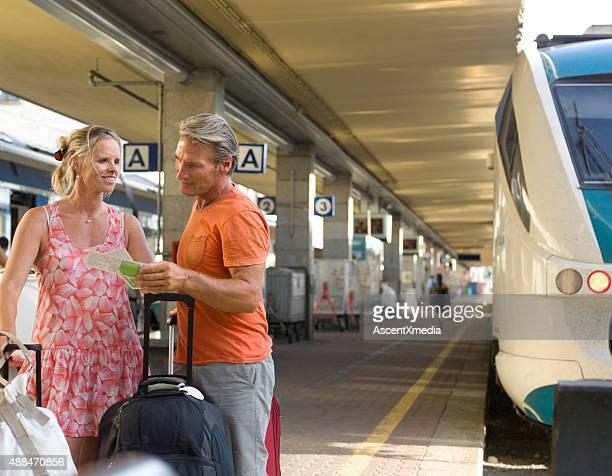 Couple wait on train platform with luggage