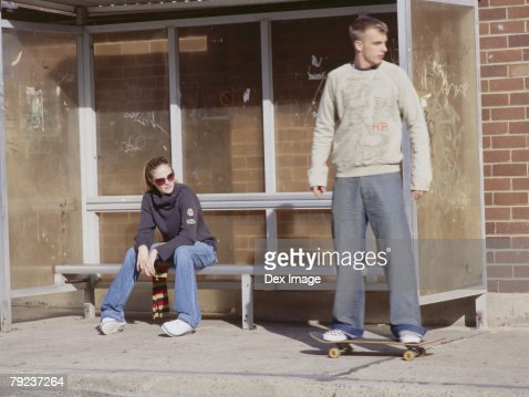 Couple waiting at bus stand : Stock Photo