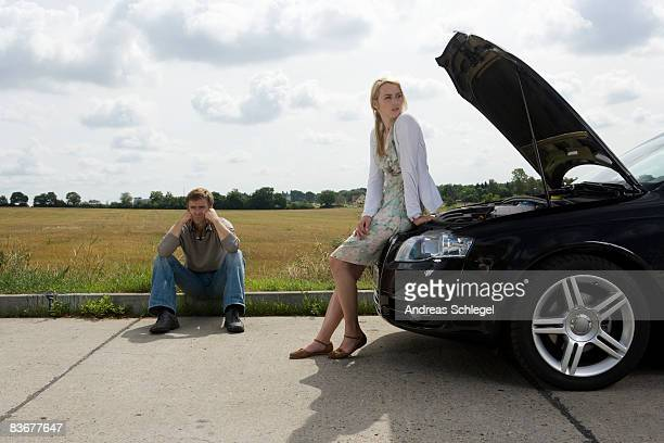 A couple waiting at the roadside for assistance with their car