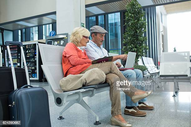 Couple waiting for plane departure and enjoying digital tablet.