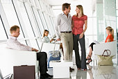 Couple waiting with other airline passengers in departure gate