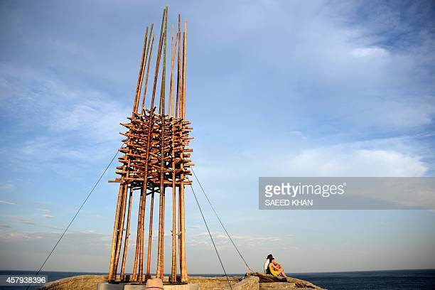 A couple waits for the sunset next to a sculpture by artist Cave Urban of Australia titled 'save our souls' overlooking Sydney's coastline on October...