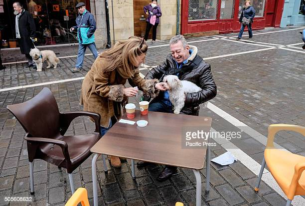 A couple waits with her dog to be anointed outside the Saint Nicolas church in Pamplona