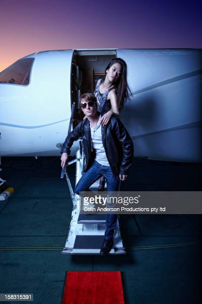 Couple waking down steps of private jet