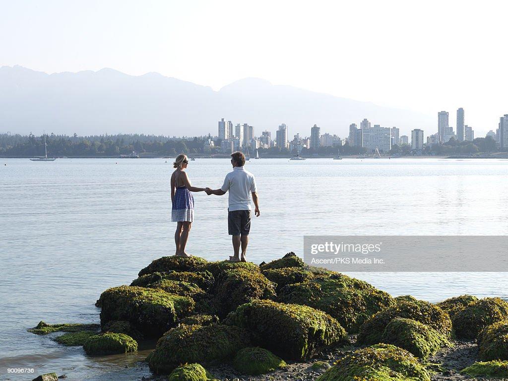 Couple walk across tidal rocks at Kitsalano beach : Stock Photo