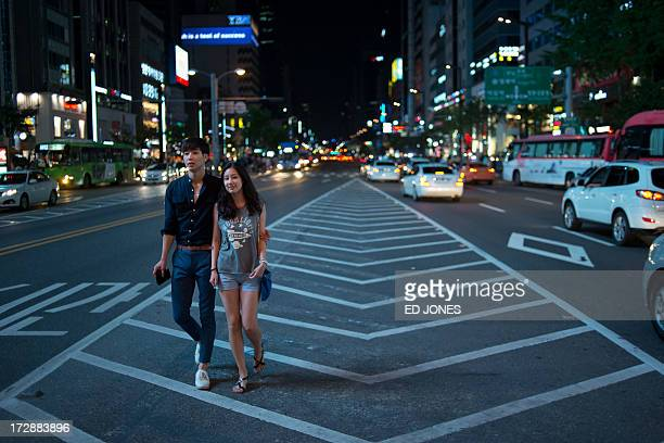 A couple walk along a main road in the Gangnam district of Seoul on July 5 2013 One of Asia's most affluent countries South Korea is the region's...