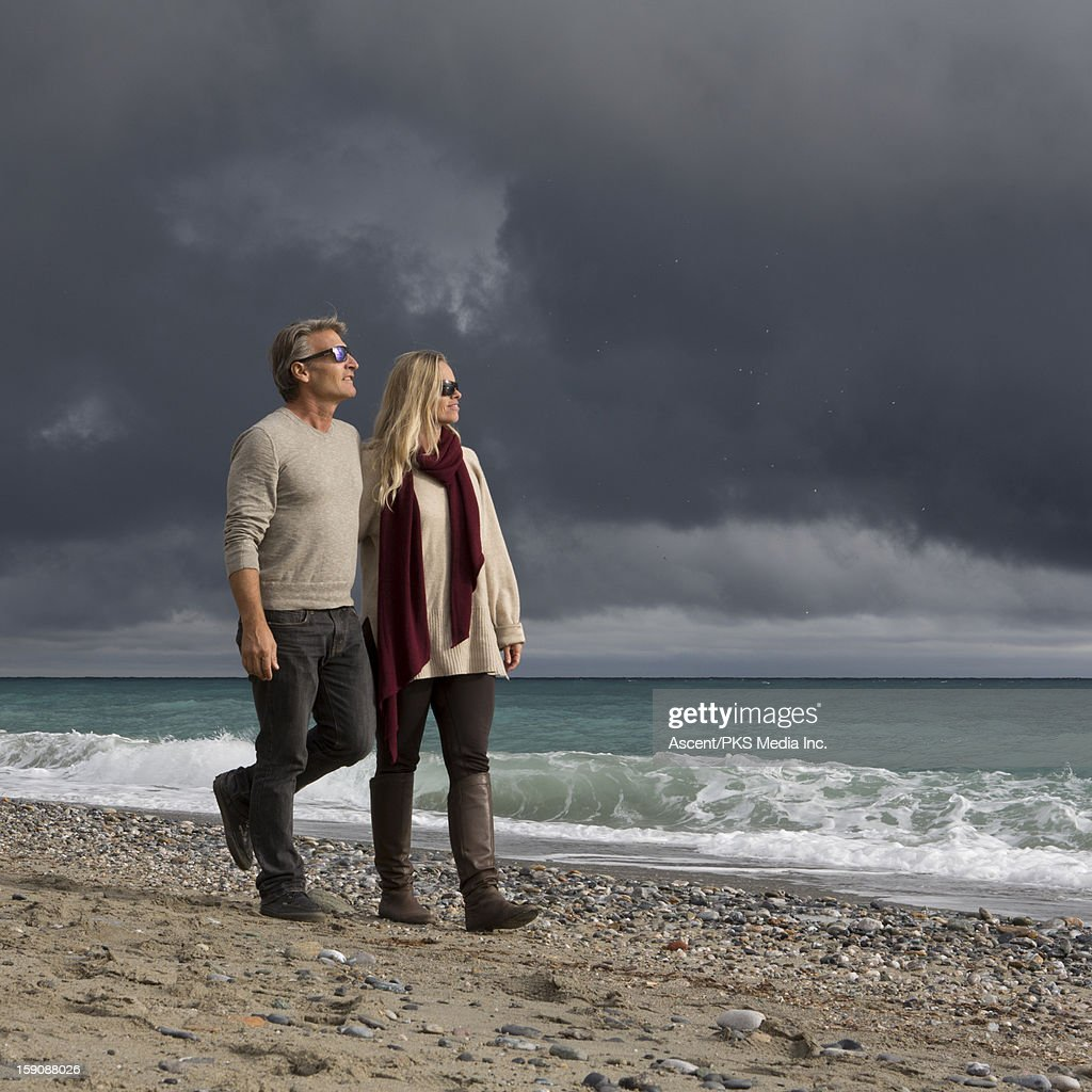 Couple walk along beach after storm clouds pass : Stock Photo