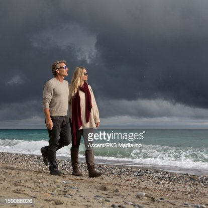 Couple walk along beach after storm clouds pass : Stock Photo