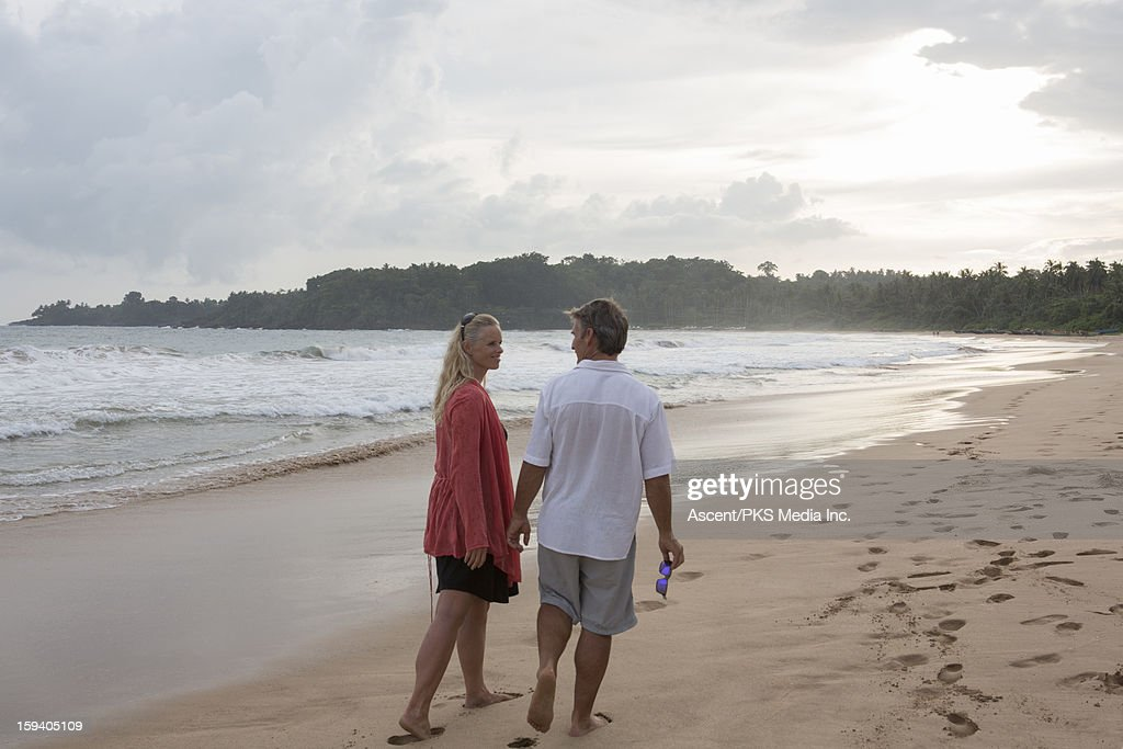 Couple walk along beach at sunset, surf behind : Stock Photo