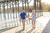 Couple walk along beach below wooden pier