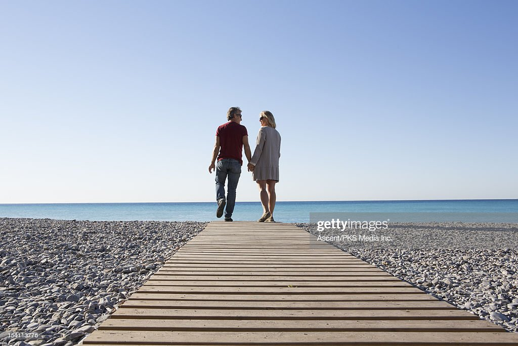 Couple walk along boardwalk over pebble beach, sea