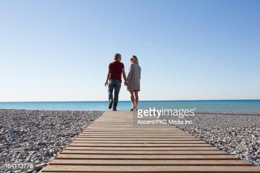 Couple walk along boardwalk over pebble beach, sea : Stock Photo