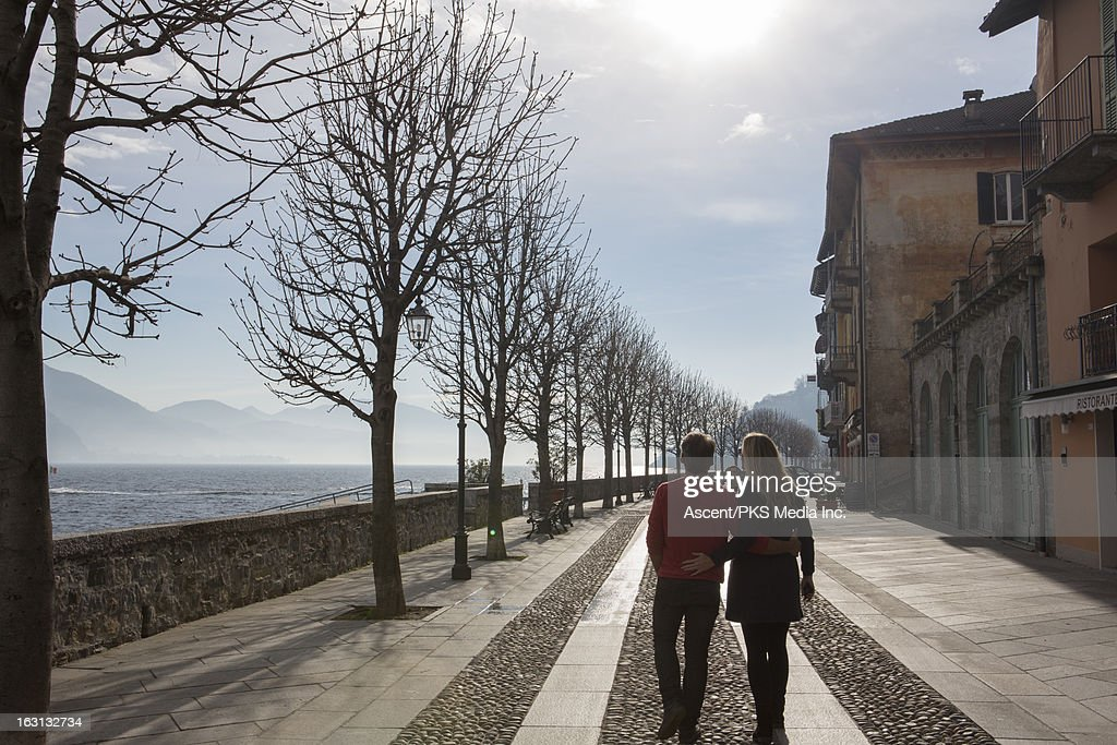 Couple walk along cobblestone path, old town : Stock Photo