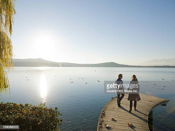 Couple walk along curving lake pier, autumn leaves