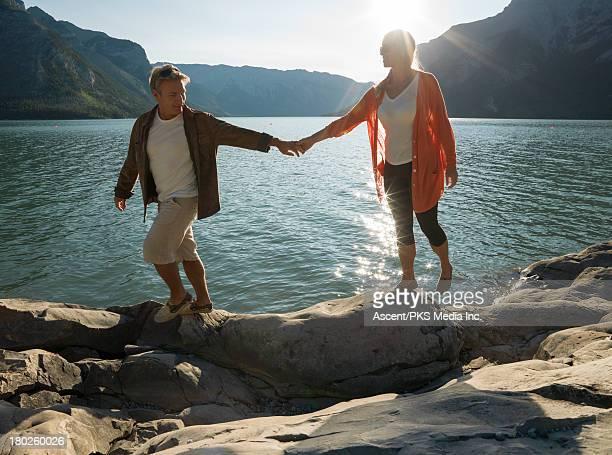 Couple walk along edge of mtn lake, hand in handa