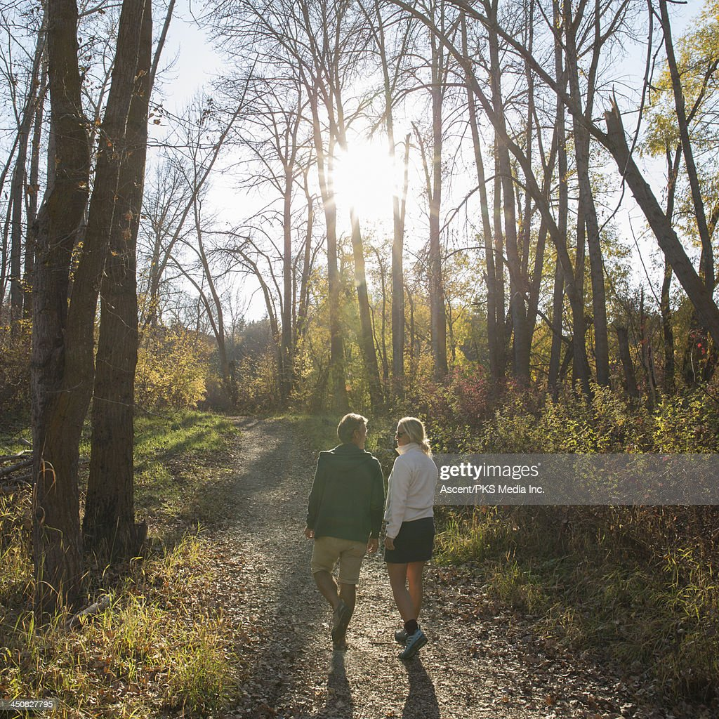 Couple walk along forest path in autumn : Stock Photo