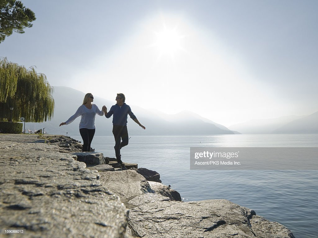 Couple walk along lakeshore, hand in hand : Stock Photo