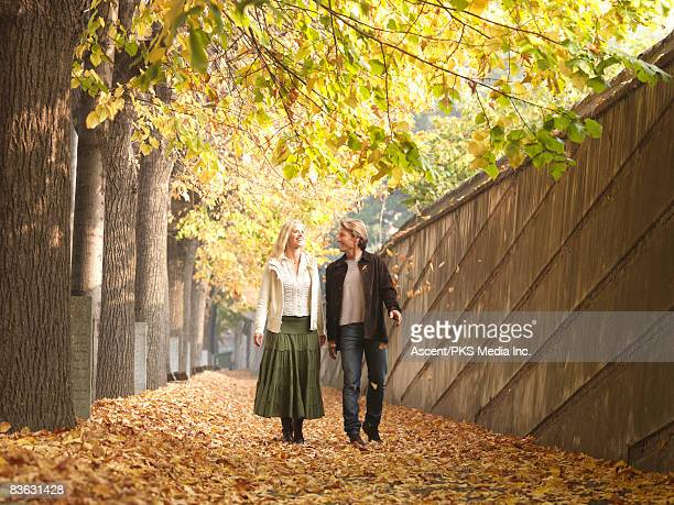 Couple walk along pathway with falling leaves