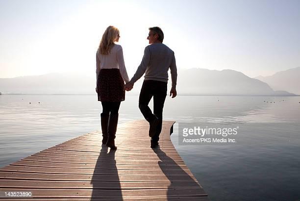 Couple walk along pier, towards tranquil lake