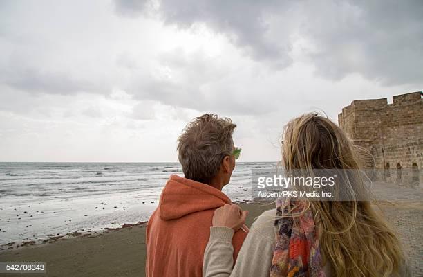 Couple walk along seaside promenade, fortress