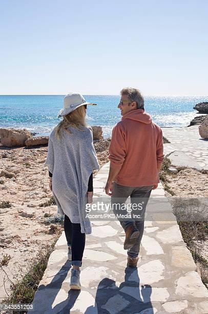 Couple walk along stone pathway to sea