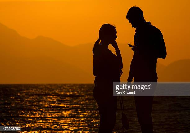 A couple walk along the beach at sunset on May 31 2015 in Kos Greece Migrants are continuing to arrive on the Greek Island of Kos from Turkey who's...