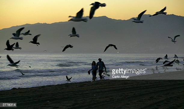 A couple walk along the beach in Santa Monica California December 2 2003 on a warm evening as much of the east coast was plunged into a deep freeze