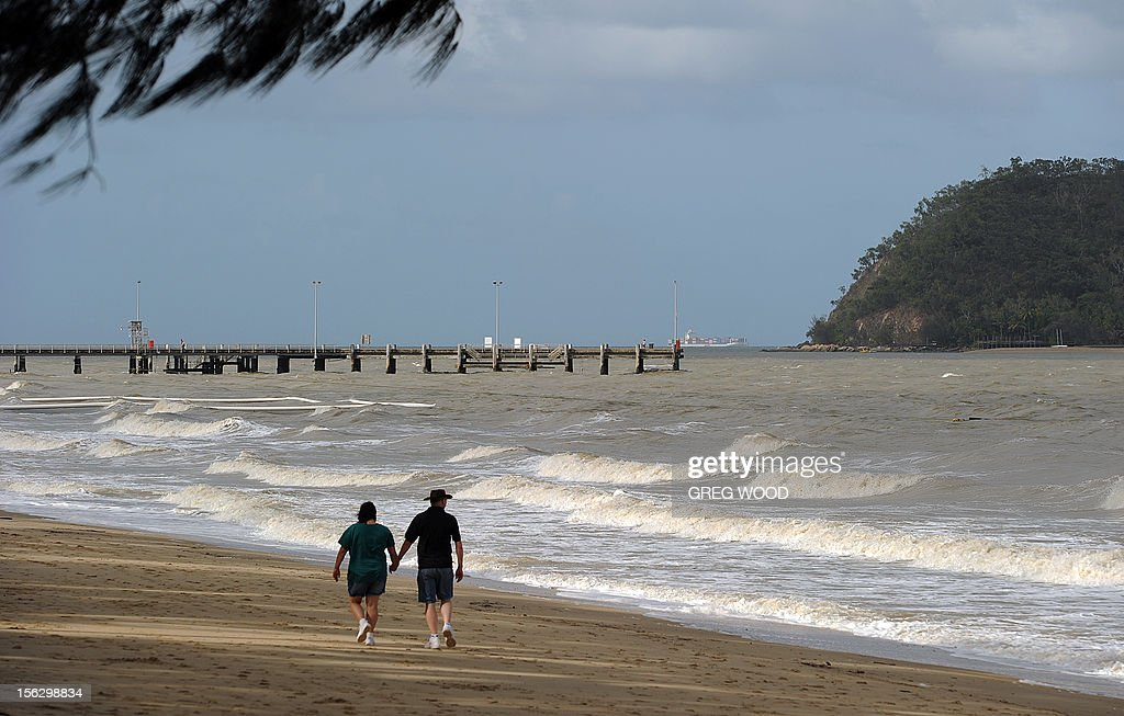 A couple walk along the foreshore at Palm Cove in Tropical North Queensland on November 13, 2012. Tens of thousands of people were flocking to Australia's laid-back tropical north for a total solar eclipse on November 14, a phenomenon officials say has not been seen in the region in 1,300 years. AFP PHOTO / Greg WOOD
