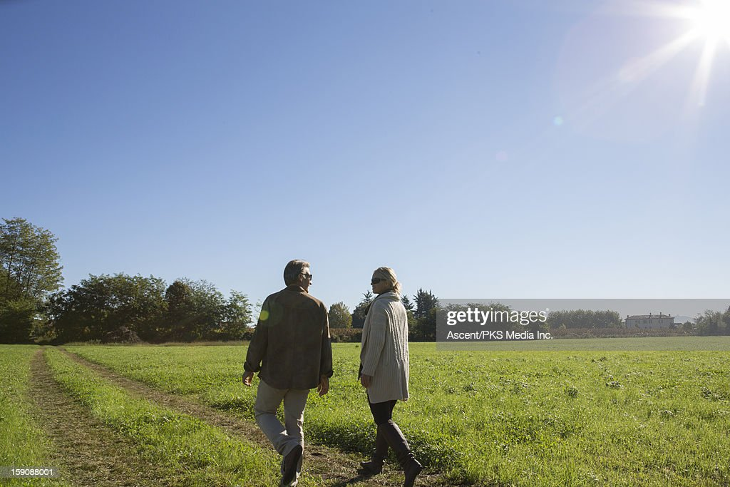 Couple walk along track through green field : Stock Photo