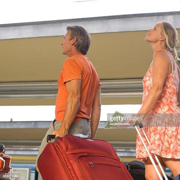 Couple walk along train platform with luggage