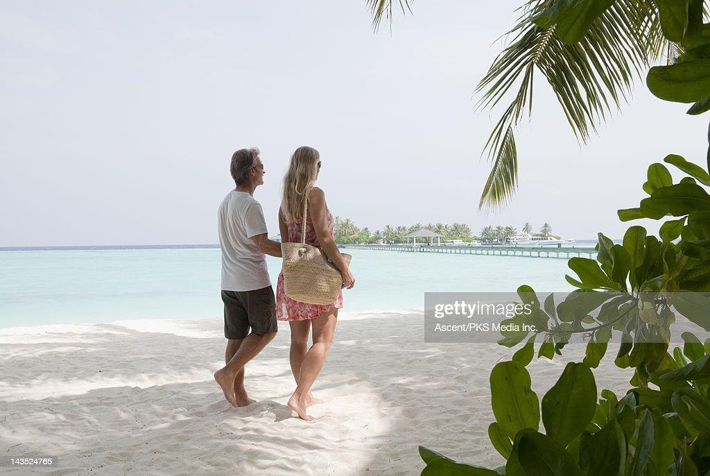 Couple walk along white sand beach, pier behind : Stock Photo