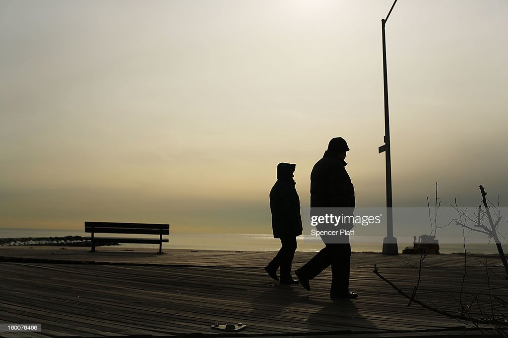 A couple walk down the remainder of the boardwalk in the Rockaways on January 25, 2013 in the Queens borough of New York City. Three months after Sandy devastated parts of New York and New Jersey, hundreds of residents are still without electricity and heat and depend on churches and charities to meet their basic needs. This past week saw some of the coldest temperatures of the winter hit parts of New York.