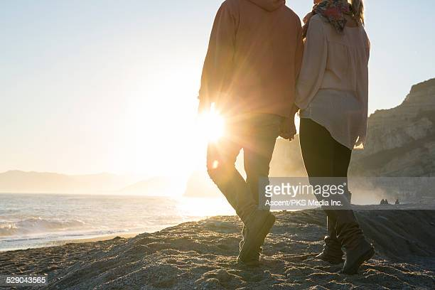 Couple walk hand in hand along beach, sunrise