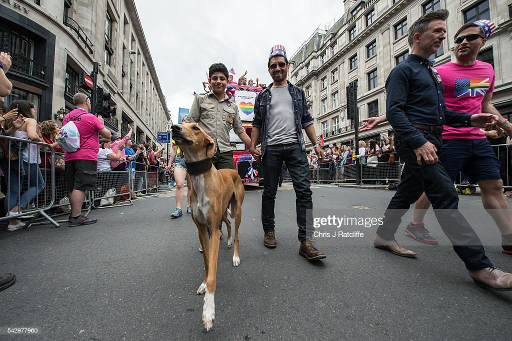 A couple walk hand in hand with their dog whilst wearing Ameican flag hats as the LGBT community celebrates Pride in London on June 25, 2016 in London, England. Across the city performances and speeches take place as a parade makes it way through the centre ending in Trafalgar Square. 2016 Pride in London comes just two weeks after Omar Mateen shot dead 50 people at Pulse, a gay nightclub in Orlando, Florida.