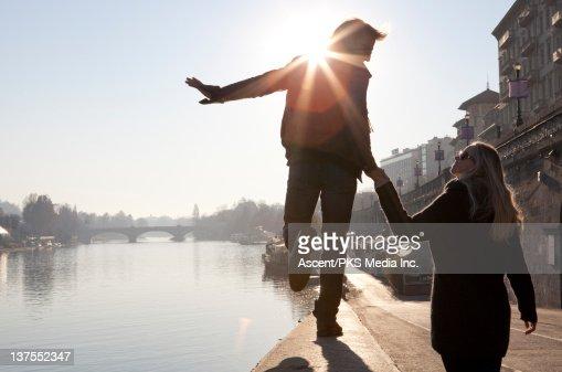 Couple walk in balance along stone river wall,city : Stock Photo