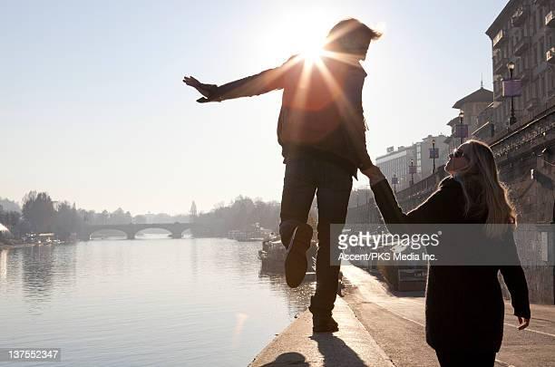 Couple walk in balance along stone river wall,city