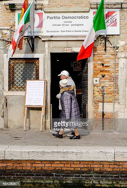 A couple walk in front of a Democratic Party polling station during today primary elections on December 8 2013 in Venice Italy Italians are voting...