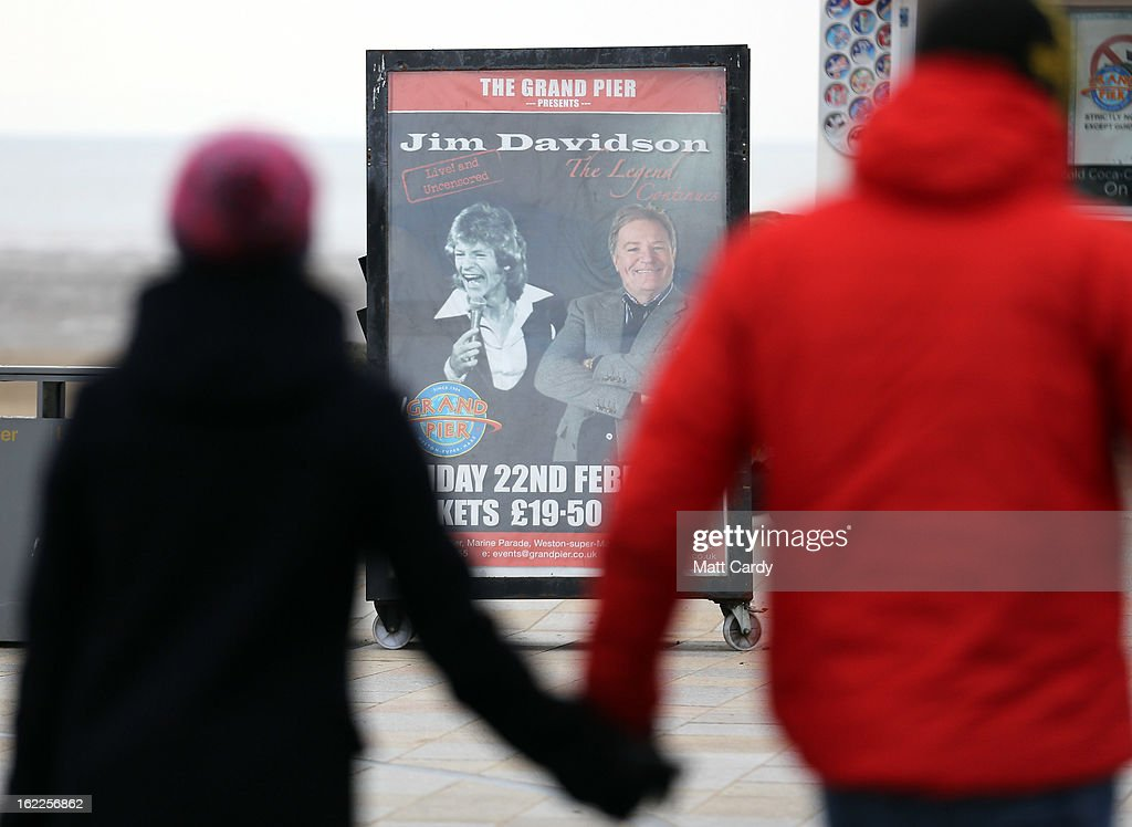 A couple walk in front of a poster advertising a Jim Davidson performance at the Grand Pier on February 21, 2013 in Weston-Super-Mare, England. According to recently released figures by the Ministry Of Justice, Weston-super-Mare has the highest rate of divorce in the UK.