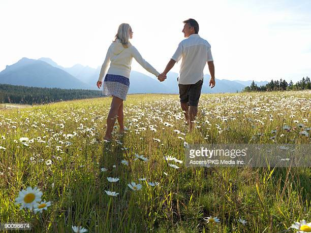 Couple walk in mountain meadow of daisies