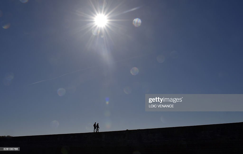 A couple walk on a pier in Saint-Gilles-Croix-de-Vie, western France, on May 4, 2016. / AFP / LOIC