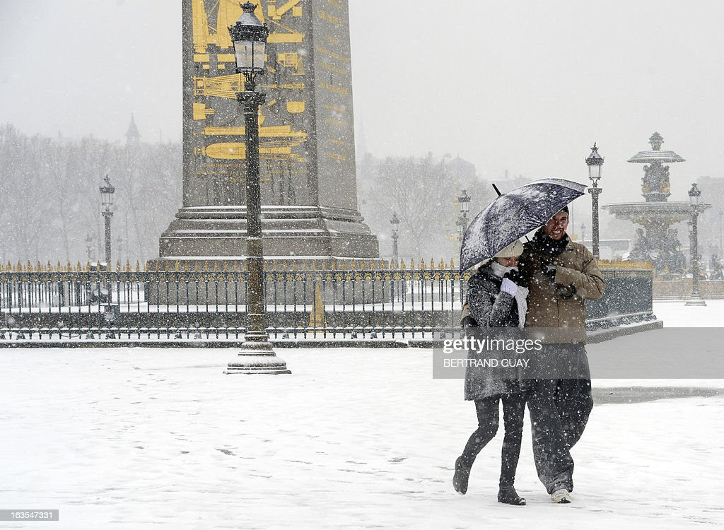 A couple walk on a snowy sidewalk on Place de la Concorde in Paris, on March 12, 2013, during a heavy snow storm on France. More than 68,000 homes were without electricity in France and hundreds of people were trapped in their cars, officials and weather services said today. Twenty-six regions in northwest and northern France were put on orange alert because of heavy snowfalls, which Meteo France said were 'remarkable for the season because of the expected quantity and length of time'.