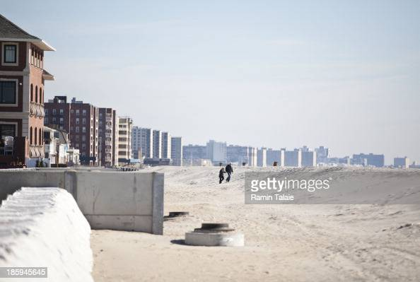 A couple walk on newly constructed sand dunes at Rockaway Beach on October 265 2013 in the Belle Harbor section in the Queens borough of New York...
